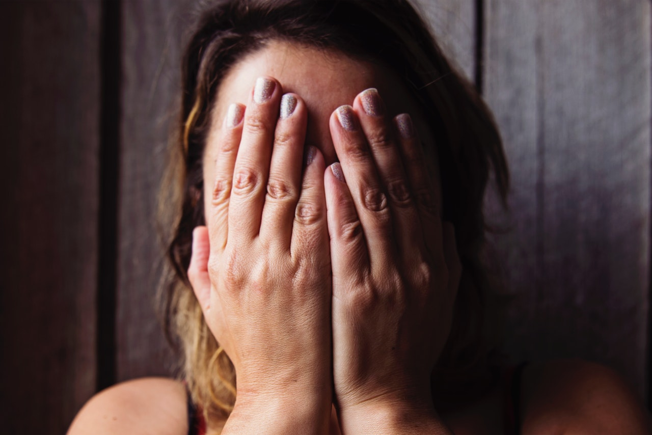 guilt and shame woman covering her face