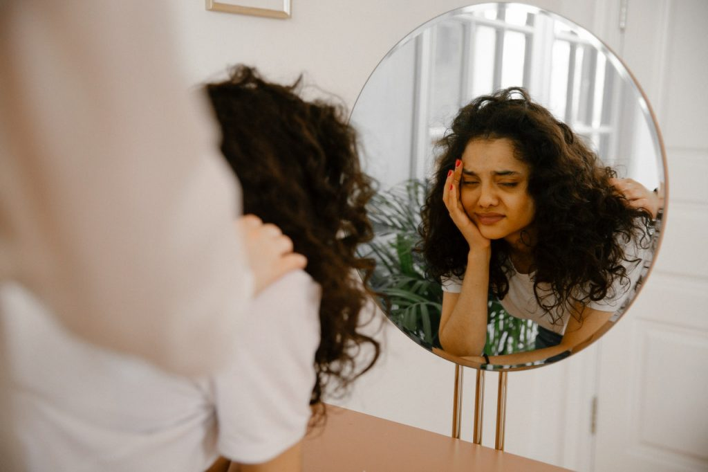 What is Self esteem, reflection of sad woman in mirror
