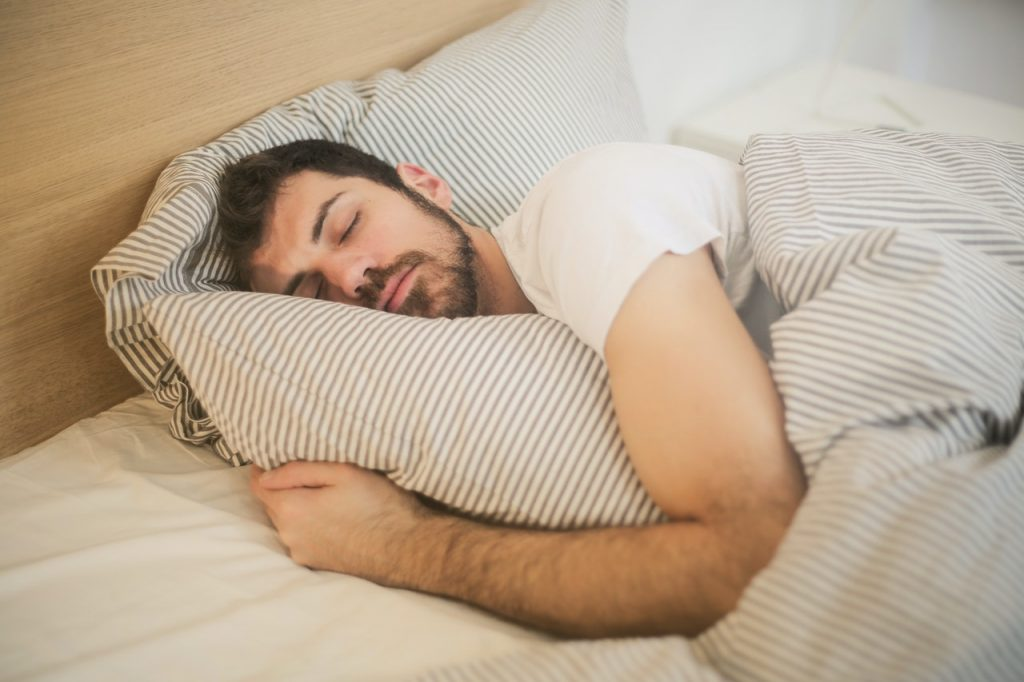 Sressed man relieving stress sleeping in bed