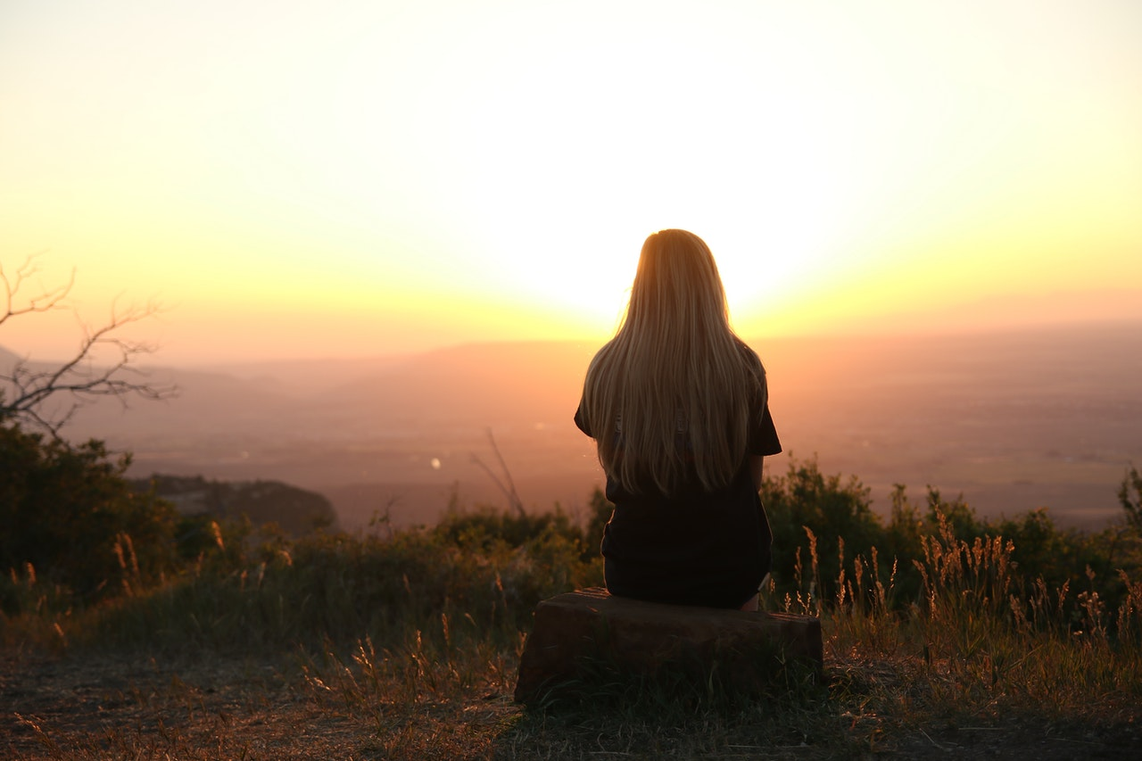 Forgiveness of Self woman sitting on hill